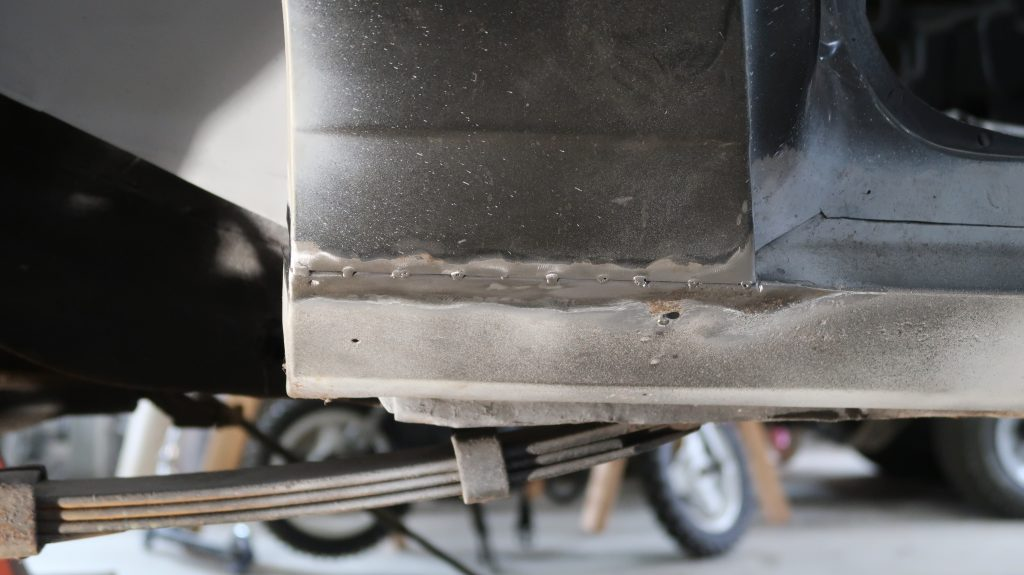 Passenger's side quarter panel tack welded to rocker panel.